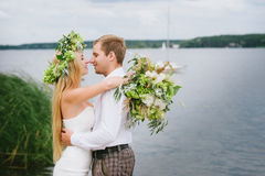 Happy young couple with a bouquet and a wreath embracing and kissing Stock Photos