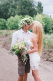 Happy young couple with a bouquet and a wreath embracing and kissing Stock Image