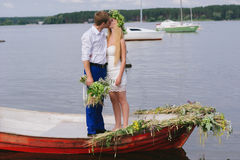 Happy young couple with a bouquet and a wreath embracing and kissing Royalty Free Stock Photos