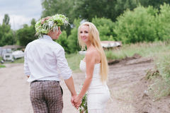 Happy young couple with a bouquet and a wreath embracing and kissing Stock Photography