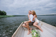 Happy young couple with a bouquet and a wreath hug sitting in a boat on the lake and sky background Stock Photos