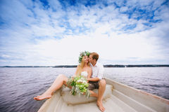 Happy young couple with a bouquet and a wreath hug sitting in a boat on the lake and sky background Royalty Free Stock Image