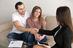 Happy young couple and broker manager handshaking after signing. Cheerful young couple shaking hands with bank worker after signing loan contract, banking credit Royalty Free Stock Photo