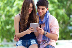 Happy young couple browsing internet with digital tablet  in the Royalty Free Stock Images