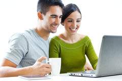 Happy young couple browsing internet at home Stock Photo