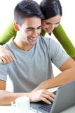 Happy young couple browsing internet at home Royalty Free Stock Image