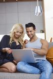 Happy young couple browsing internet at home Royalty Free Stock Photography