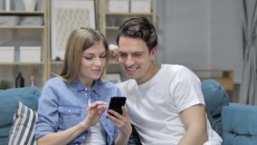 Happy Young Couple Browsing Internet on Smartphone at Home. 4k high quality, 4k high quality stock video footage
