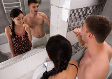 Happy young couple brushing their teeth Royalty Free Stock Images