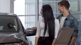 Happy young couple buying new automobile at the dealership, reading info paper. Beautiful woman and her boyfriend examining automobile for sale. Couples, cars stock footage