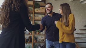 Happy young couple is buying new house shaking hands with female realtor then hugging and laughing. Relocation stock footage