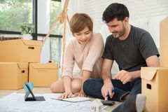 Couple planning their new moving house. Happy young couple calculating their budget for their new house. Smiling each other stock photo