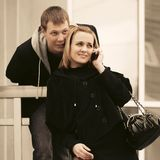 Happy young couple calling on cell phone on city street royalty free stock photography