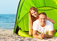 Happy young couple camping on the beach Stock Images
