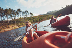 Happy young couple canoeing on lake Royalty Free Stock Photography