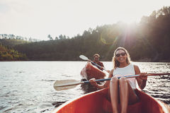 Happy young couple canoeing on summer day Stock Image