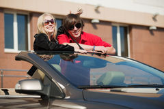 Happy young fashion couple in a car Royalty Free Stock Photo