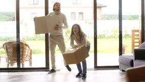 Happy couple carrying boxes entering new house, home owners moving stock footage