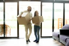Happy couple holding boxes entering house, moving in new home Royalty Free Stock Photo