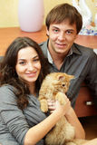 Happy young couple with a cat Stock Photos