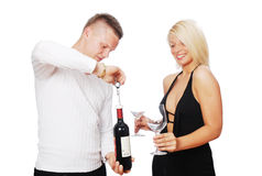 Happy young couple celebrating. Opening the red wine Stock Photo
