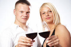 Happy young couple celebrating. A toast with red wine Royalty Free Stock Photos