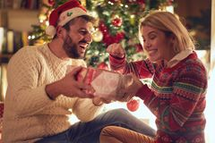 Happy young couple celebrating Christmas and having fun stock images