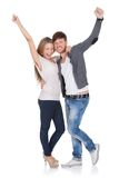 Happy young couple celebrating. Happy young couple standing close together in a loving embrace celebrating and laughing punching the air with their raised fists Stock Images