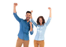 Happy young couple celebrating success with hands up royalty free stock images