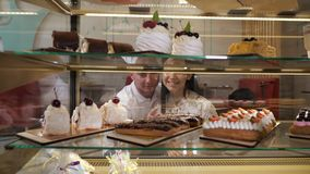 Happy couple chooses tasty cakes in glass show case of shop. Happy young couple chooses tasty fresh cakes standing in glass show case of confectionery shop close stock footage