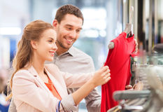 Happy young couple choosing dress in mall Stock Image