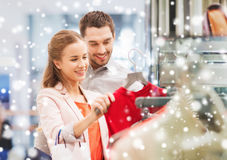 Happy young couple choosing dress in mall. Sale, consumerism and people concept - happy young couple with shopping bags choosing dress in mall with snow effect Stock Photos