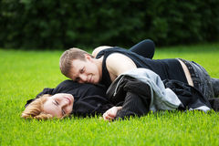 Happy young couple in a city park. Happy young couple lying on the grass Royalty Free Stock Photo