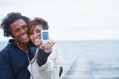 Happy young couple clicking their snap by the sea Stock Photography