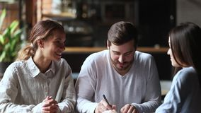 Happy young couple clients sign insurance contract handshake broker. Happy young couple clients customers sign loan investment contract agreement making sale stock video footage