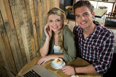 Happy young couple with coffee and laptop in cafe. High angle view of happy young couple with coffee and laptop in cafe Royalty Free Stock Photography