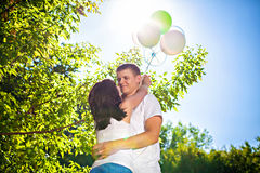 Happy young couple with colorful balloons outdoors Royalty Free Stock Photos
