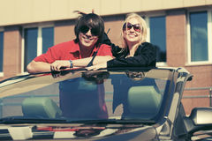 Happy young couple in convertible car Stock Photos