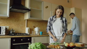 Happy young couple cooking breakfast together in the kitchen eartly morning stock video footage