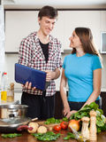 Happy young couple cooking with notebook Royalty Free Stock Photos