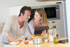 Happy young couple cooking pasta together Royalty Free Stock Image