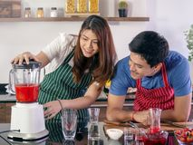 Happy young couple cooking together stock photo