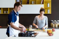 Happy young couple cooking together in the kitchen at home. Stock Photos