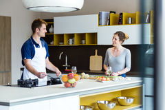 Happy young couple cooking together in the kitchen at home. Stock Images