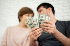 Happy Young couple counting money. Happy Young couple counting money while sitting on sofa for their new house. Saving royalty free stock photo