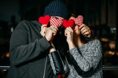Happy young couple covering each other`s eyes with red pillow he stock photography
