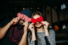 Happy young couple covering eyes with red pillow hearts and smil royalty free stock photography