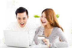 Happy young couple with credit card and  laptop Stock Images