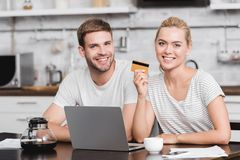 Happy young couple with credit card using laptop and smiling at camera. At home royalty free stock image