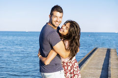 Happy young couple cuddling happy with love on a sea beach. Happy young couple on summer vacation smiling and hugging royalty free stock photo